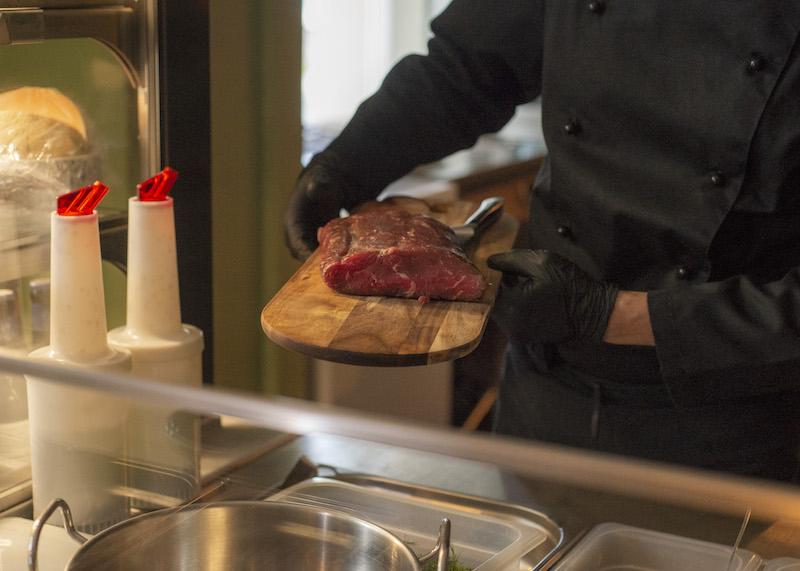 Der Koch präsentiert ein Stück Rindfleisch.